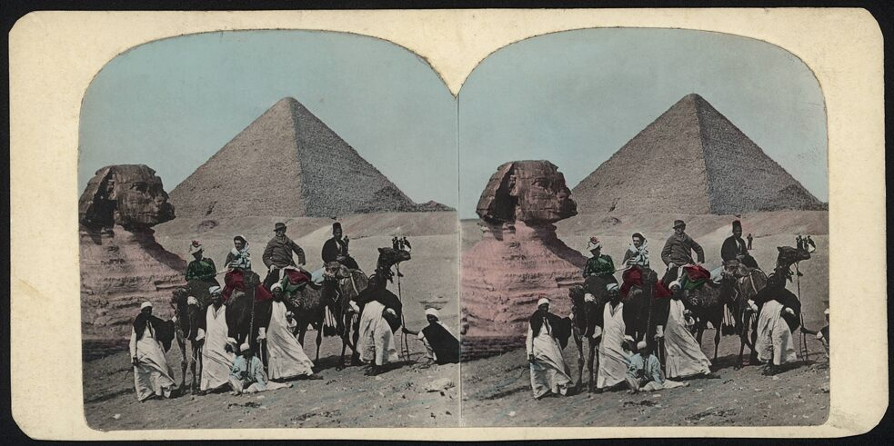 European travellers in Egypt on camels led by fellahs in Gizeh in front of the Great Sphinx with the Pyramid of Cheops in the background. Photo (stereoscopic image), anonymous, undated, 1880s. Berlin, Collection Archive for Art and History (Sammlung Archiv für Kunst und Geschichte).