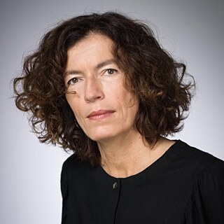 Portrait of Anne Weber against a gray background; she has curly brown hair and is wearing a black sweatshirt
