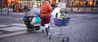 Homeless woman with two shopping trolleys