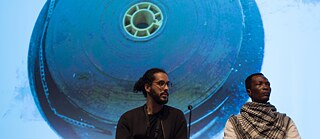 "The filmmakers Fradique from Angola and Didi Cheeka from Nigeria at a panel discussion on (de)colonial film archives at the Culturgest in Lisbon. In September 2019, the Goethe-Institut Portugal organised a series of events consisting of a panel discussion, workshop and accompanying film sessions on how to deal with film material from a colonial context as part of the international project ""Everything passes, except the past""."