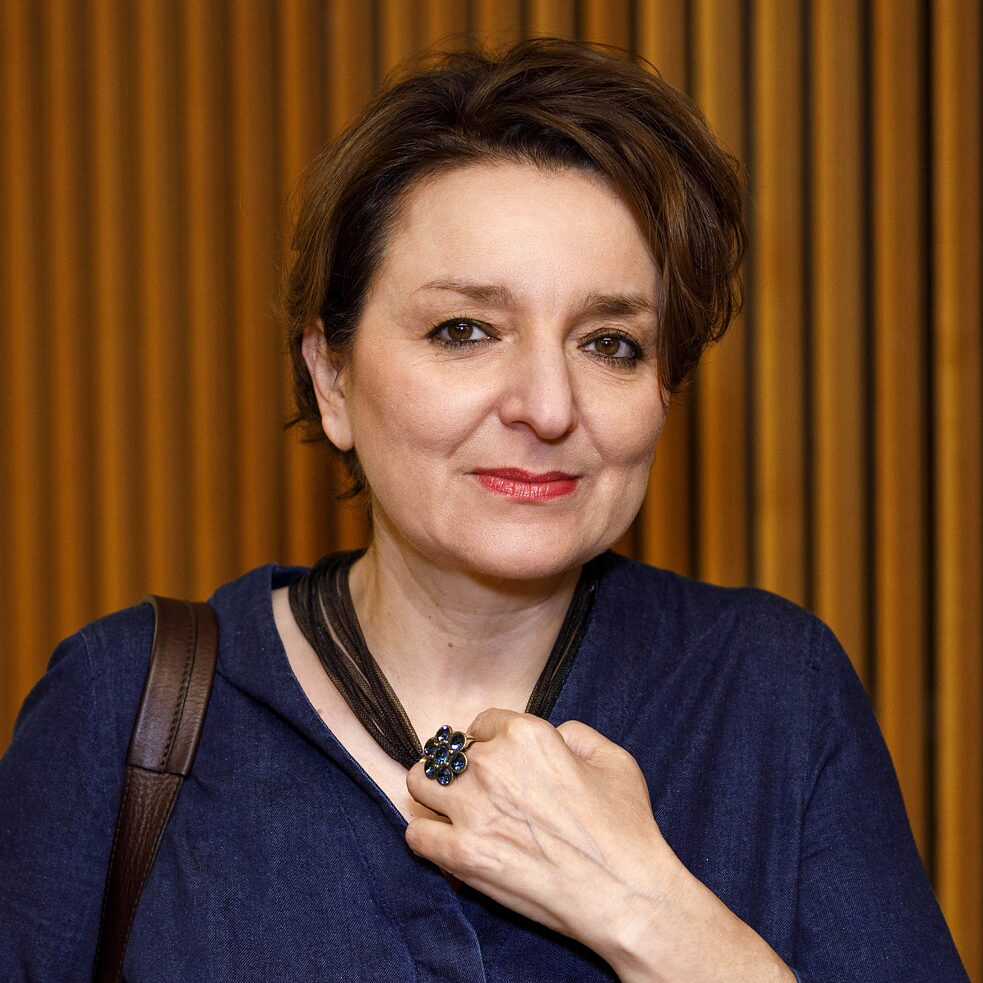 Square image of Eva Illouz against a brown backdrop; she wears short dark hair and holds a glas in her left hand