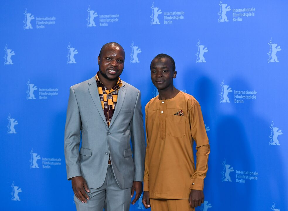 "Global South: William Kamkwamba (left) and the actor of the film ""The Boy Who Harnessed the Wind"" Maxwell Simba at the Berlinale on February 12, 2019. The film is based on the autobiography of the same name by William Kamkwamba. The Malawian-born mechanic became a hero in his home country because he built a windmill made of eucalyptus, bicycle parts and material from the local scrap yard to supply his house with electricity. Later he constructed a solar-powered water pump that supplied his village with drinking water for the first time. Because his family could not pay the school fees, Kamkwamba had to leave school. However, he continued his education in the village library, where he discovered the book ""Using Energy"" and saw in it the picture and explanation of a windmill."