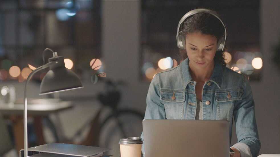 A young woman with headphones learning German on her laptop.