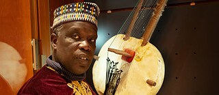 Badara Seck in front of a Kora, the African instrument with high symbolic value