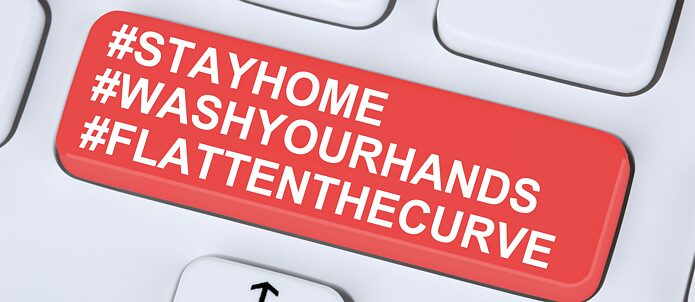 Toetsenbord met opschrift Stay at home, wash your hands, flatten the curve