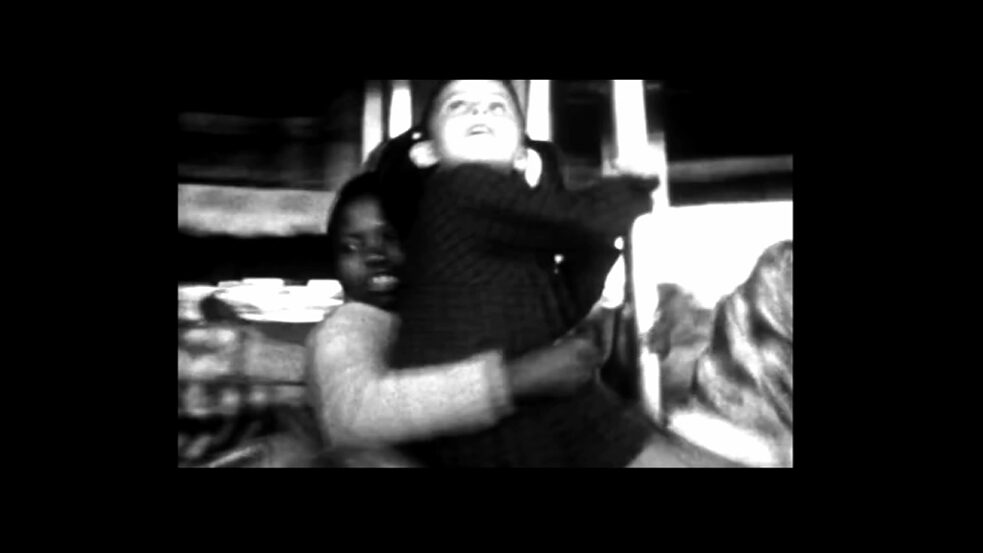 "Colonial history – The image is a screenshot from the film ""A Memory in Three Acts"". It shows a black child and a white child on a merry-go-round."