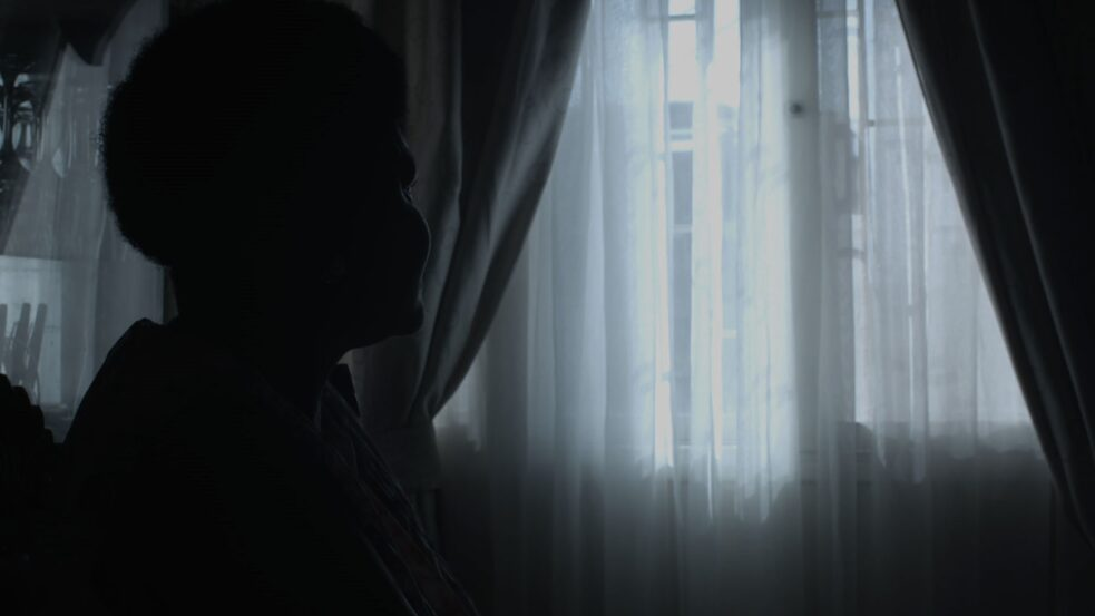 Colonial history – This screenshot depicts Isabel Langa who is sitting in a darkened room and looking out the window.