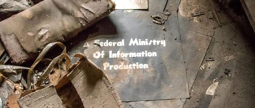 "The image captures a dusty black sign lying on the ground. In white, it reads, ""A Federal Ministry of Information Production."""