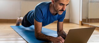 Man doing a plank and using laptop at home