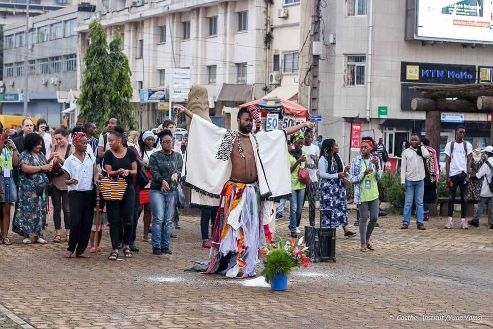 decolonial – Nashilongweshipwe Mushaandja brings the street in front of the former censorship board in Yaoundé with performers and his audience to a standstill.