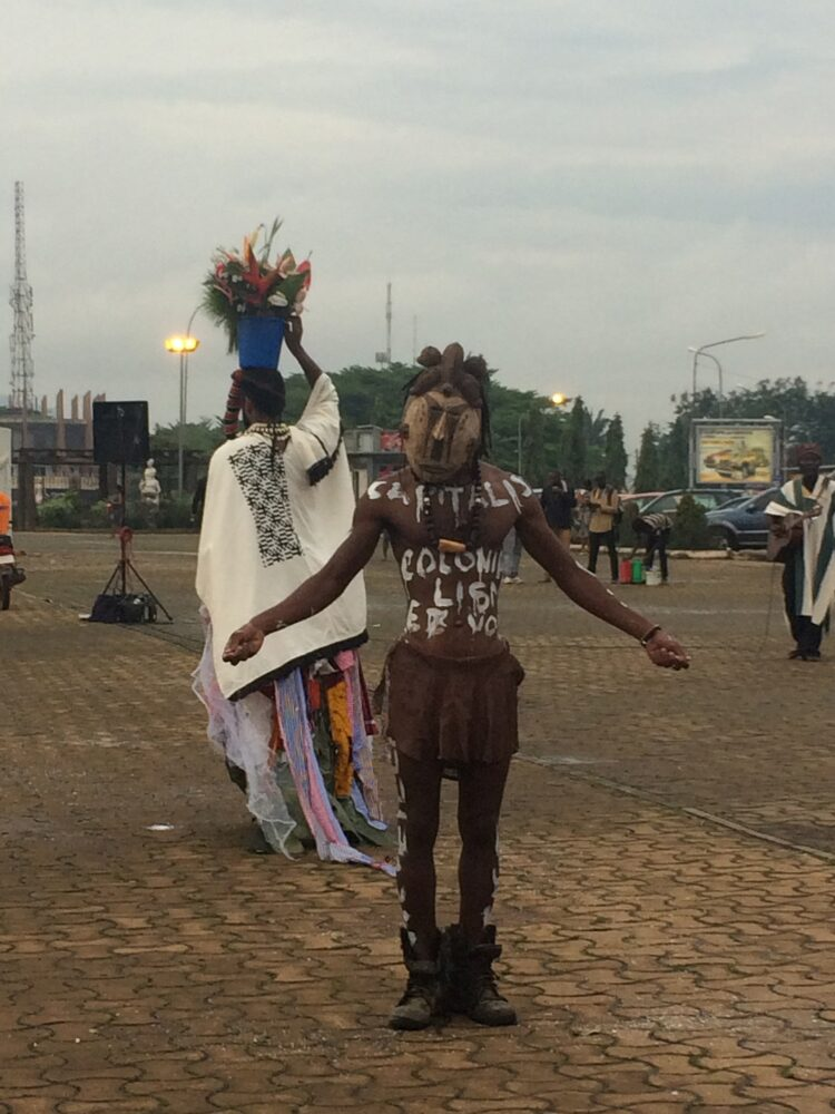 "decolonial – Nashilongweshipwe Mushaandja performed ""The Dance of the Rubber Tree"" in the middle of the Independence Square in Yaoundé. Every now and again, hawkers ran through the production to sell their wares. Until some stopped to watch the performance."