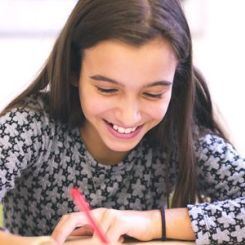 Young girl studying and laughing.
