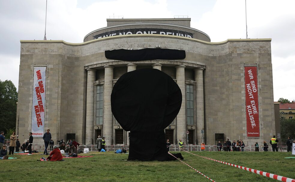 """We are not your backdrop"": In spring 2020, Berlin's ""Volksbühne"" theatre covered its sign and the ""robber's wheel"" on Rosa Luxemburg Square to distance itself from the corona demonstrations taking place there, which were increasingly taken over by right-wing extremist forces."