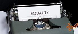 The picture shows a typewriter with a piece of paper on which the word Equality has been typed.