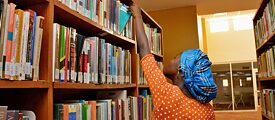 A young Nigerian woman takes a book from a bookshelf in a library.