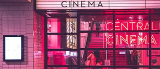 Exterior view of a pink illuminated cinema.