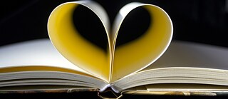 The pages of an open book forming a heart.