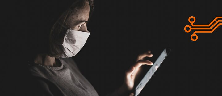 A woman with a mask looks at her smartphone.