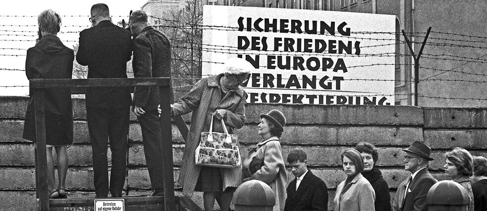 Berlin, 1962. People stand on a stage on the Western side of the Berlin Wall in order to catch a glimpse at the other side of the border.