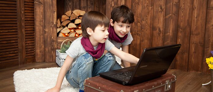 two kids sitting in front of a computer