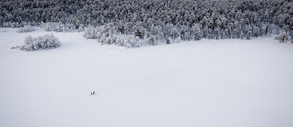 A snowy landscape from above, two people wading through the snow
