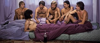 "Film still from Rosa von Praunheim's ""It Is Not the Homosexual Who Is Perverse, But the Society In Which He Lives"": a group of naked men sit on a mattress"