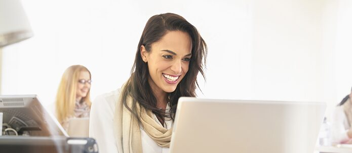 Smiling woman on computer wearing a white blouse and a beige scarf. In the background another woman at the computer out of focus.