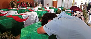 Restitution – July, 4, 2020: A man rests on a coffin of one of the 24 Algerians at the Moufdi-Zakaria culture palace in Algiers. After decades in a French museum, the skulls of 24 Algerians decapitated for resisting French colonial forces were formally repatriated to Algeria in an elaborate ceremony.