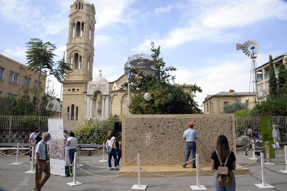 The installation at Faneromeni Square, in front of an Orthodox church, between two roll-up banners. Ten visitors are standing or walking around the wall.