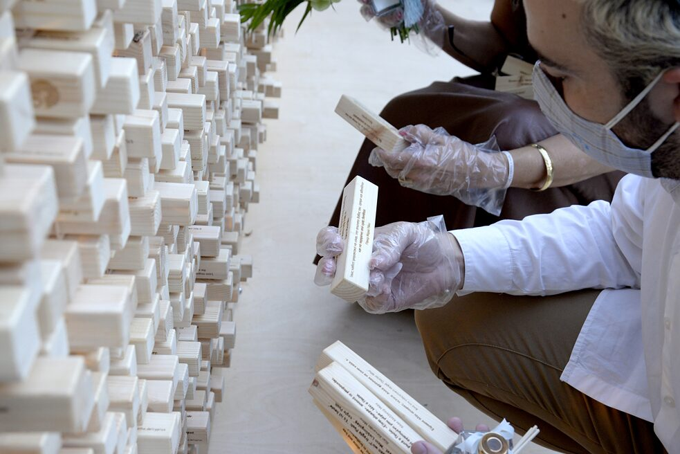 A man with a face mask is crouching in front of the wall and has three wooden blocks in his hands. He is reading the quote on the block in his right hand.