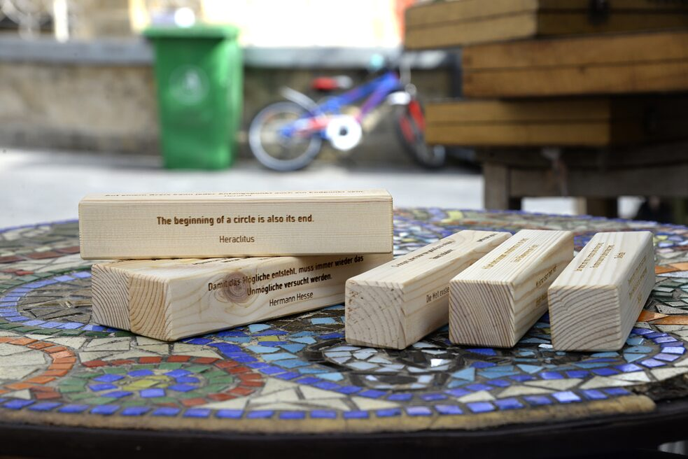 Close up of five wooden blocks placed on a table. On two of them one can read quotations from Heraclitus and Hermann Hesse.