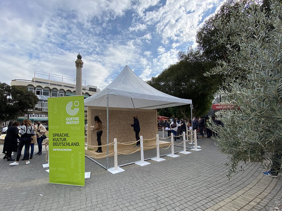 The installation at Sarayönü Square, in front of the Dikilitas column, under an awning. In front of it is the banner of the Goethe-Institut and next to it are groups of people.