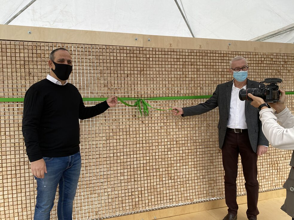 The Ambassador and the Turkish Cypriot Mayor of Nicosia are standing in front of the installation and are about to untie a green ribbon. Someone is holding a camera in front of them.