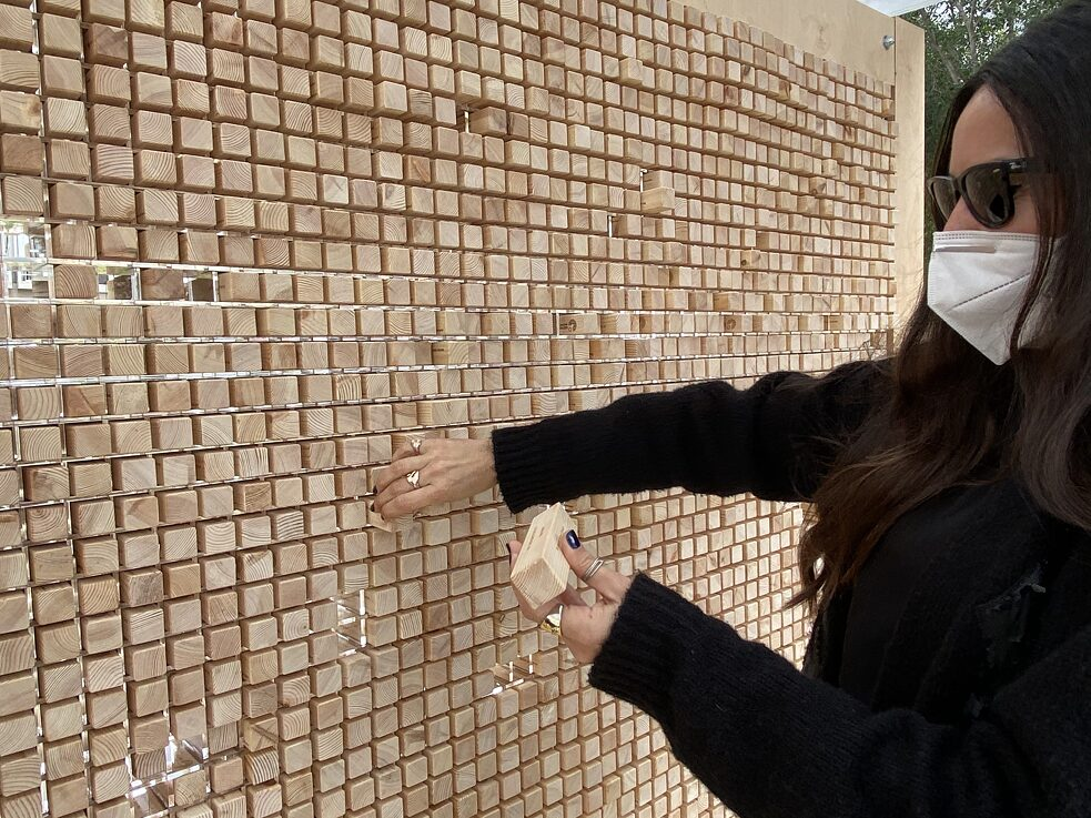 Close-up of part of the wall filled with wooden blocks. A woman in a black pullover wearing sunglasses and a mask is holding a block in one hand and reading from it, while pulling another block from the wall with the other hand.