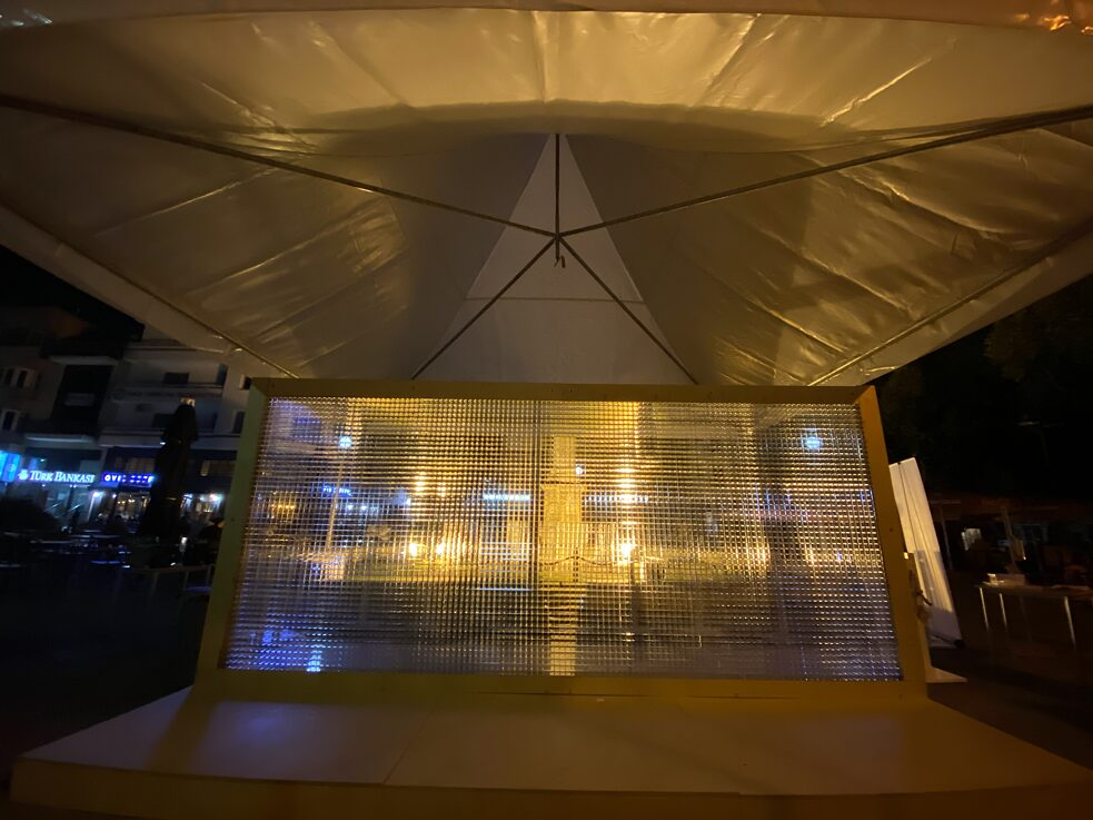 Night picture. The whole installation, which consists of a wooden frame, a wooden base and a transparent plexiglass frame, is set under a tent.