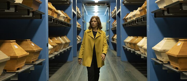 "Still frame from the Netflix Serie ""The last word"": Karla Fazius (Anke Engelke) in the cremtory, walking through a hallway which is filled with shelves full of new coffins."