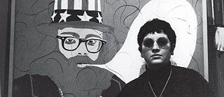 Image from the film PARIS CALLIGRAMMES by Ulrike Ottinger: short-haired woman with round sunglasses stands in front of a mural