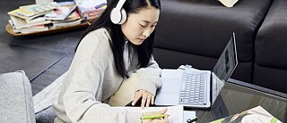 A young woman with headphones sitting at her laptop taking notes.