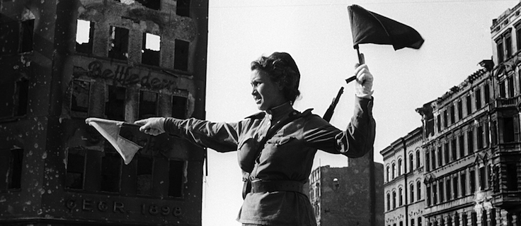 A woman in the Red Army directs traffic in Berlin 1945.