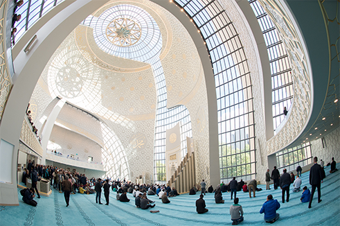 The construction of the new Central Mosque in Cologne is a clear indication that mosque architecture has outgrown the rear courtyard. Inside 1,800 stucco slabs create a geometric pattern on the walls, and an enormous chandelier features Arabic calligraphy.
