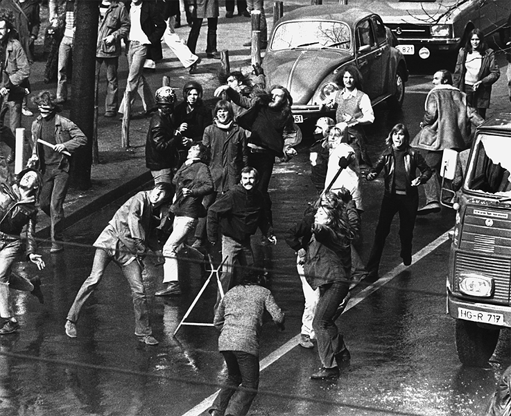 After the forced evacuation of an occupied house was announced, a street battle between police and the participants of a spontaneous demonstration took place in Frankfurt's Westend on March 28, 1973. Demonstrators used sticks and stones to defend themselves against water cannons and tear gas.