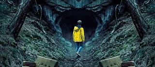 A young man in a yellow rain coat in front of the opening of a large cave