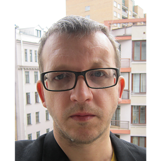 Head shot Oleg Nikiforov; he wears short hair and black rectangular glasses;  in the background buildings