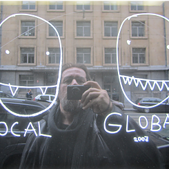 Dan Perjovschi takes a selfie in a reflecting window; on the glass, two heads are drawn, underneath it says local and global