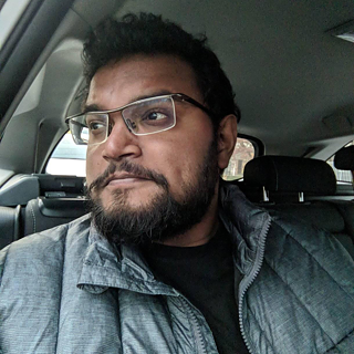 Portrait of Yudhanjaya Wijeratne; he is sitting in a car and wears short hair and glasses