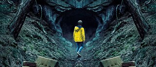 A young man wearing a yellow raincoat at the entrance of a cave in a forest