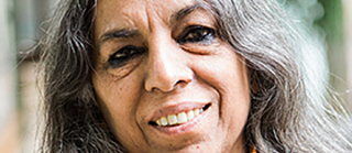 Portrait of Urvashi Butalia;  she has long gray-black hair and smiles into the camera